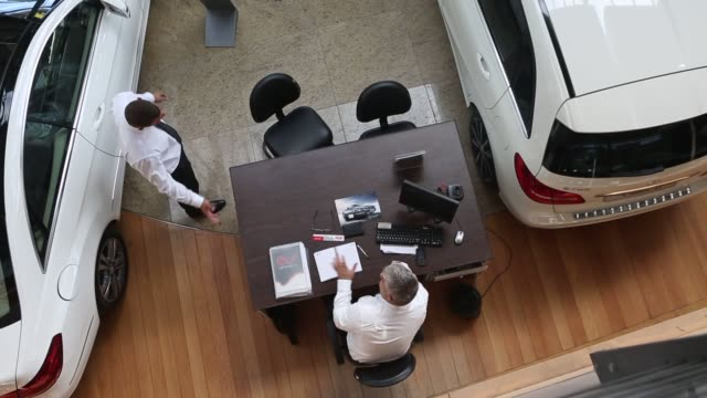 A salesman works at his desk bottom left at the AGO Mercedes Benz dealership in the Barra da Tijuca neighborhood of Rio de Janeiro Brazil Overhead...