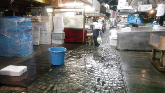 salesmen at the tsukiji market in tokyo clean after busy business day - einzelner senior stock-videos und b-roll-filmmaterial