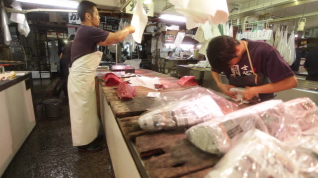 Salesmen at the Tsukiji Market in Tokyo preparing fish for sale
