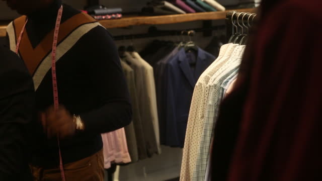"vídeos de stock e filmes b-roll de salespeople help shoppers look for clothes in a bonobos ""guide shop"" in greenwich, connecticut, u.s. on sunday, october 21, 2018. - cabine de loja"