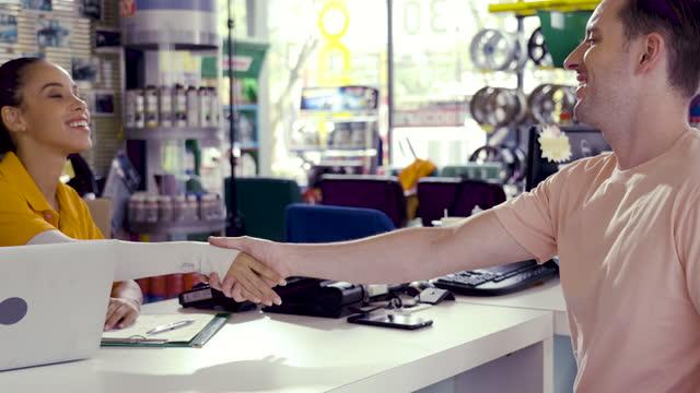vidéos et rushes de vendeur et client au service de voiture ou au magasin d'automobile. - partie de véhicule