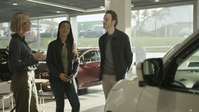 vídeos y material grabado en eventos de stock de saleswoman advising couple on car purchase in vehicle dealership showroom - vendedor