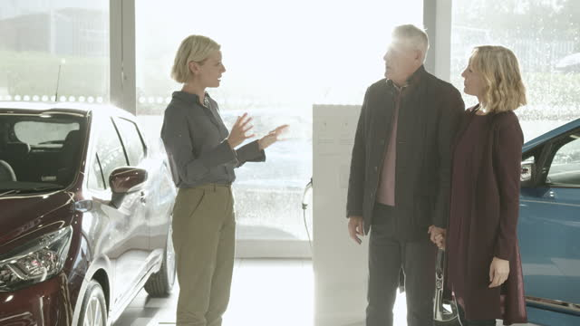 vídeos y material grabado en eventos de stock de saleswoman advising mature couple on car purchase in electric vehicle dealership showroom - vendedor