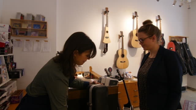 Saleswoman and customer at checkout counter in guitar workshop