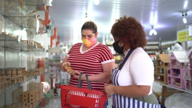 commessa e cliente in negozio - indossando la maschera facciale - strategia di vendita video stock e b–roll