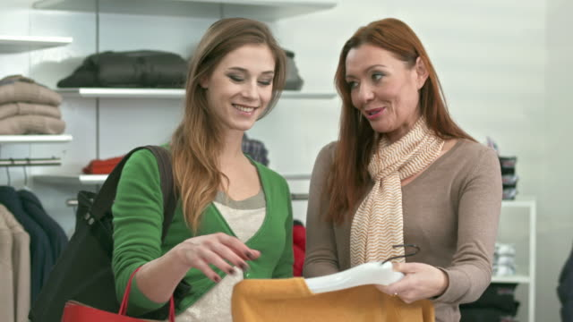 HD: Saleswoman Assisting Young Woman In Boutique