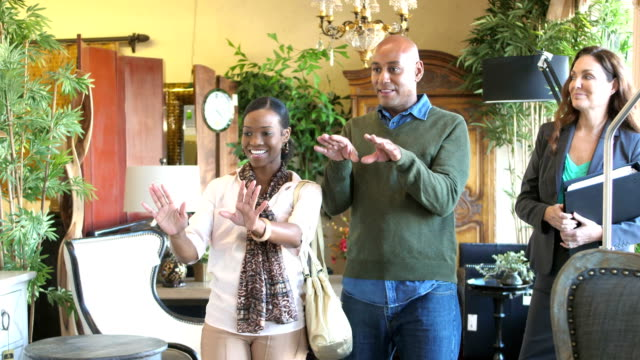 Saleswoman helping African-American couple buy furniture
