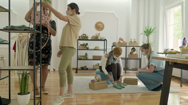 vídeos de stock e filmes b-roll de saleswoman helping female customer with her choice in fashion store during coronavirus pandemic - viciado em compras