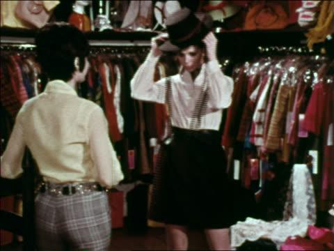 vidéos et rushes de 1969 saleswoman helping woman try on hat in clothing store / greenwich village, nyc - société de consommation