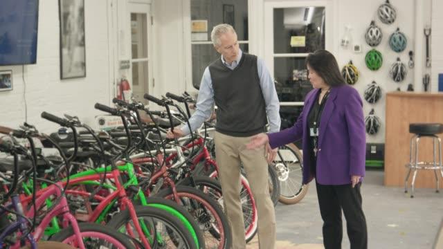 vidéos et rushes de vendeuse, contribue à une boutique homme mûr pour un vélo électrique - équipement de musculation