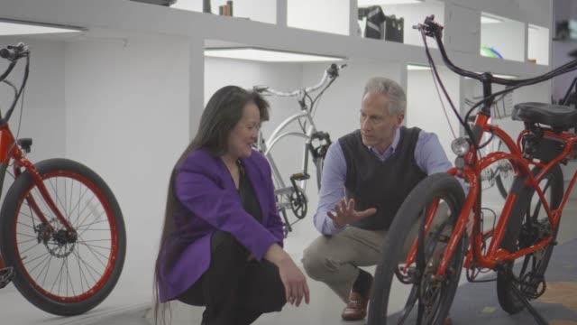 vidéos et rushes de vendeuse, contribue à une boutique homme mûr pour un vélo électrique - vendre