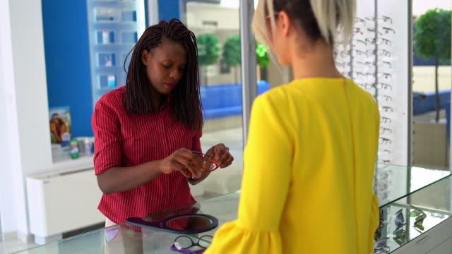 セールスウーマンは美しい若い女性が眼鏡を選ぶのを助ける - めがね点の映像素材/bロール