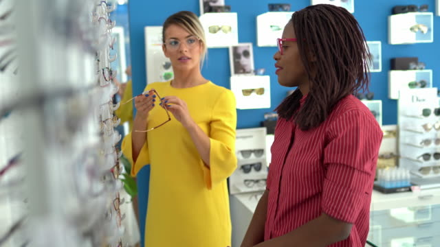 saleswoman helps beautiful young woman choose glasses - sunglasses stock videos & royalty-free footage