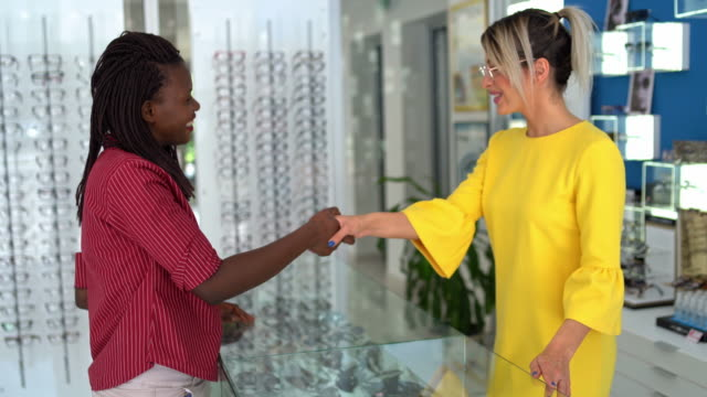 saleswoman helps beautiful young woman choose glasses - optometrist stock videos & royalty-free footage