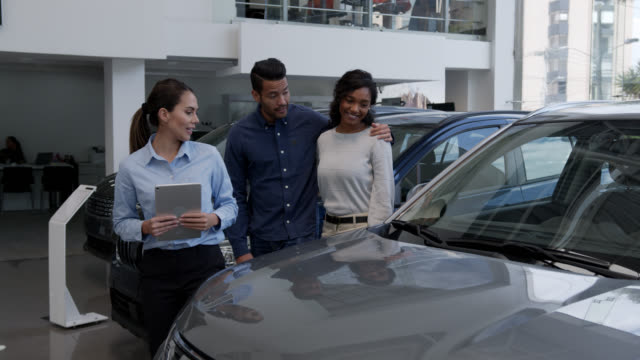 saleswoman holding a tablet showing cars to a happy diverse couple at the dealership - selling stock videos & royalty-free footage