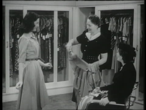 b/w 1944 saleswoman holds dress up to woman to show customer - dress stock videos & royalty-free footage
