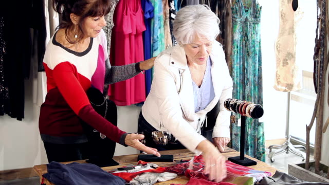 saleswoman in clothing store helps customer - boutique stock videos & royalty-free footage