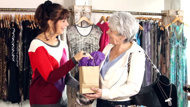 Saleswoman in clothing store helps customer