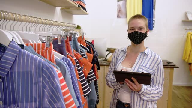 verkäuferin in gesichtsmaske mit tablet-pc im laden - casual clothing stock-videos und b-roll-filmmaterial