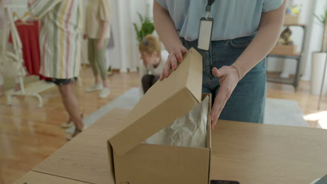 vídeos de stock e filmes b-roll de saleswoman packing shoes in shoe box at women's fashion store - viciado em compras