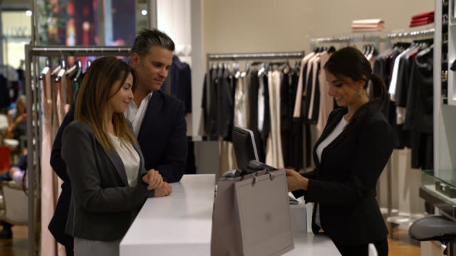 saleswoman passing credit card on eftpos and giving the purchase to a client couple who are looking very happy - clothing store stock videos & royalty-free footage