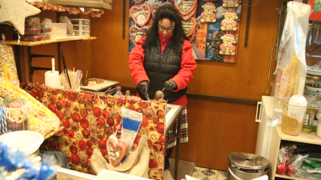 a saleswoman prepares chocolate apes and puts them in the glass cabinet exterior shots of a christmas market with christmas decoration in germany - advent calendar stock videos & royalty-free footage