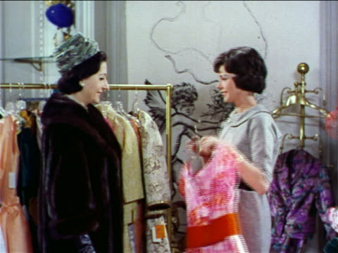 1962 saleswoman showing clothing to female customer in store / industrial