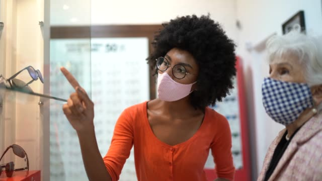 saleswoman showing eyeglasses to customer in an optical store, both wearing face mask - reading glasses stock videos & royalty-free footage
