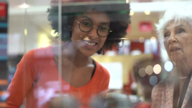 saleswoman showing products at store window to a senior customer - window display stock videos & royalty-free footage