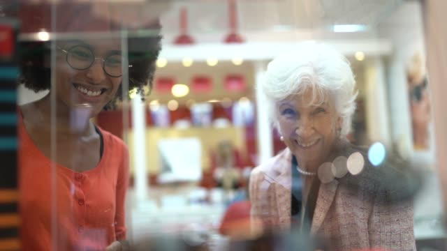 saleswoman showing products at store window to a senior customer - customer focused stock videos & royalty-free footage