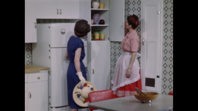 MS TS Saleswoman shows kitchen to customer / United States