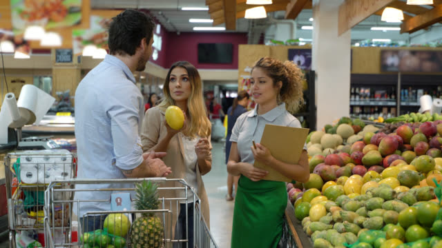 saleswoman suggesting some fruits to customer couple at the supermarket - assistant stock videos & royalty-free footage