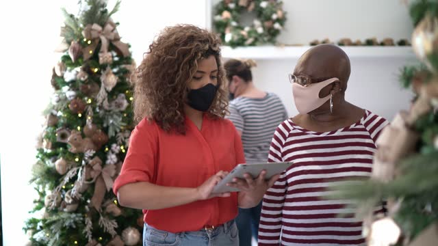 saleswoman supporting a customer in a christmas ornament store showing christmas tree - public celebratory event stock videos & royalty-free footage