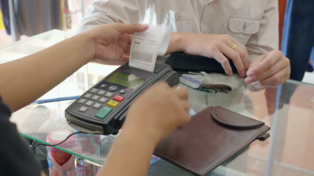 saleswoman swiping credit card through credit card reader in boutique - financial bill stock videos and b-roll footage