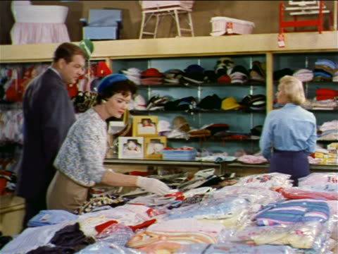 vidéos et rushes de 1962 saleswoman talking to couple shopping in clothing department of department store - homme dans un groupe de femmes