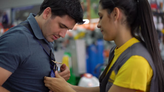 saleswoman teaching a customer how to put on a safety harness smiling - imbracatura di sicurezza video stock e b–roll