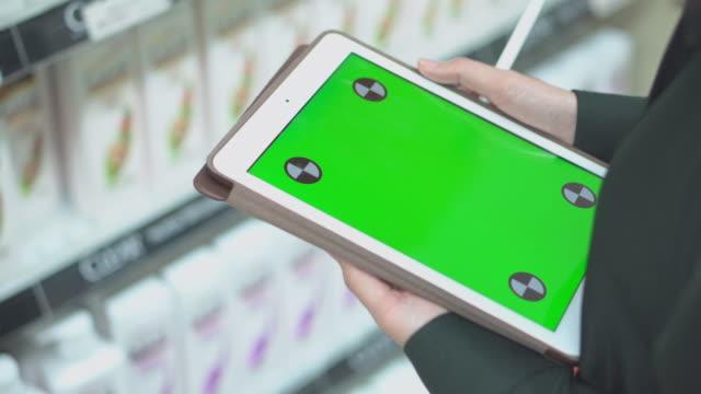 vídeos y material grabado en eventos de stock de vendedora usando tableta digital revisa productos en supermercados, pantalla verde - lapiz