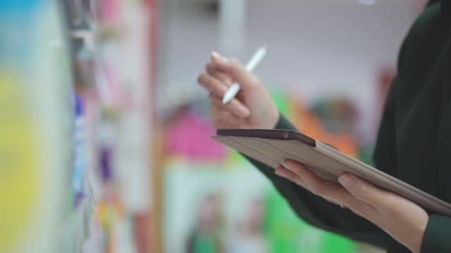 vídeos y material grabado en eventos de stock de la vendedora usando tabletas digitales revisa los productos en supermercados, slow motion - lapiz