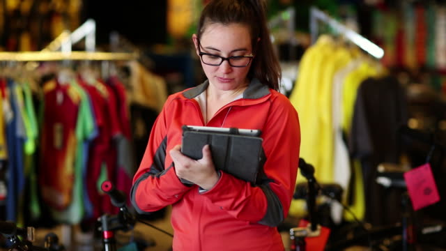 ms saleswoman using her tablet at her bicycle shop / santa fe, new mexico, united states - clothes shop stock videos and b-roll footage