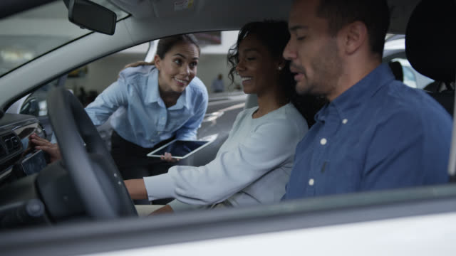 saleswoman working at a dealership showing a car to a happy diverse couple trying to make a sale - mode of transport stock videos & royalty-free footage