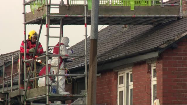 salford suspected arson attack: mother of four children who died is still in induced coma; salford: ext forensic officers on scaffolding in front of... - リチャード・パロット点の映像素材/bロール