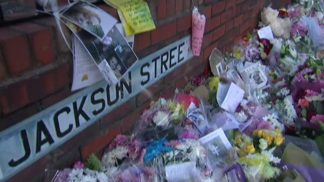Mother of four children who died is still in induced coma Salford EXT Floral tributes below road sign 'Jackson Street' Forensic officer along...