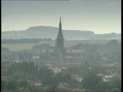 england 0240 salisbury cathedral as seen in distance over rooftops wilts track along road as cathedral seen scaffolding round salisbury tower spire... - spire stock videos & royalty-free footage