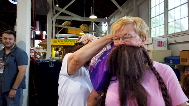 Sally Fairchild and Barb McMickle of Cedar Rapids Iowa wear a fake beards for a laugh during the Beard Growing Competition in the Farm Bureau Pioneer...
