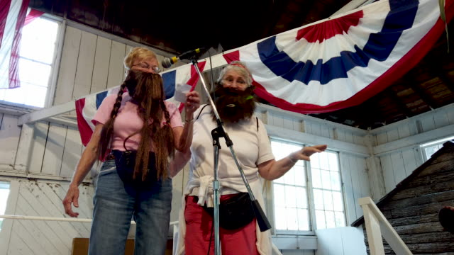 Sally Fairchild and Barb McMickle of Cedar Rapids Iowa wear a fake beards as they lead the audience in singing the Iowa State Fair Song during Beard...