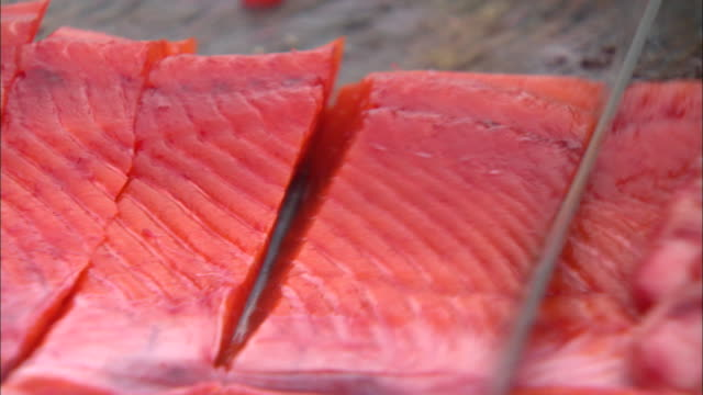 salmon being cut with a knife in alaska, usa - salmone animale video stock e b–roll