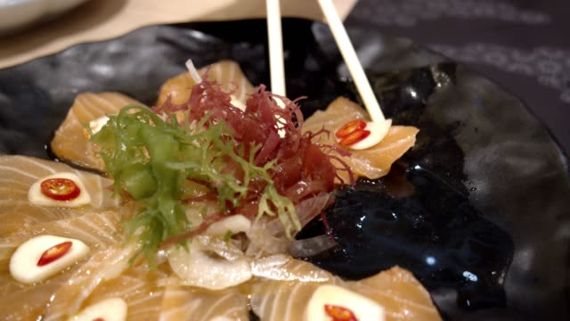 salmon sashimi spicy salad on black dish in the restaurant.japanese food style - sashimi stock videos & royalty-free footage