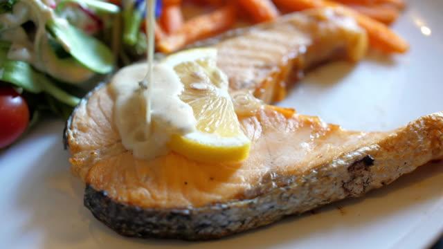 salmon steak with lemon butter sauce , slow motion - salmon steak stock videos & royalty-free footage