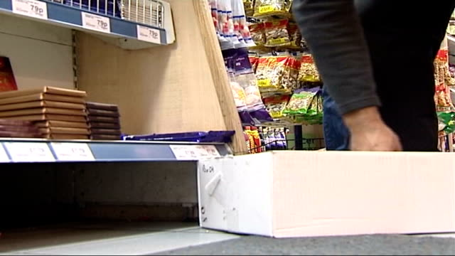 cadbury admits giving false information about level of risk; lib low angle shot of hands taking packs of cadbury chocolate bars off supermarket shelf... - salmonella video stock e b–roll
