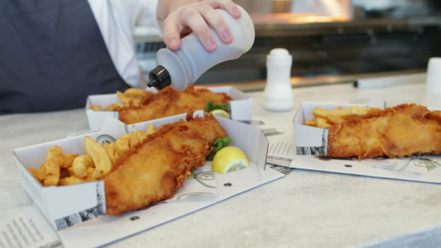 salt and vinegar on fish and chips - less than 10 seconds stock videos & royalty-free footage